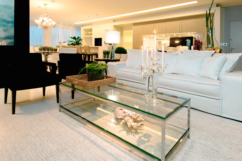 O diferencial do projeto do arquiteto Ivan Wodzinsky é a integração não apenas da sala de estar com a sala de jantar, mas também com a cozinha. Por se tratar de um apartamento no litoral, Ivan optou por cores claras, com toques em preto, que segundo o arquiteto, sofisticam o ambiente. O charme do projeto é complementado pela mistura de elementos luminotécnicos, com iluminação direta, difusa e indireta.