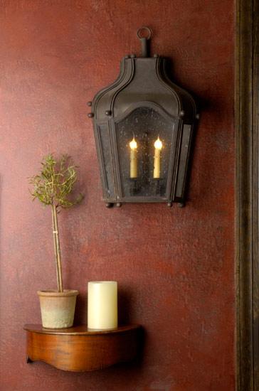 Na parede foi colocada uma mesinha com um vaso de planta e uma vela branca que combina com o propósito da decoração, que é deixar o ambiente com aspecto rústico.