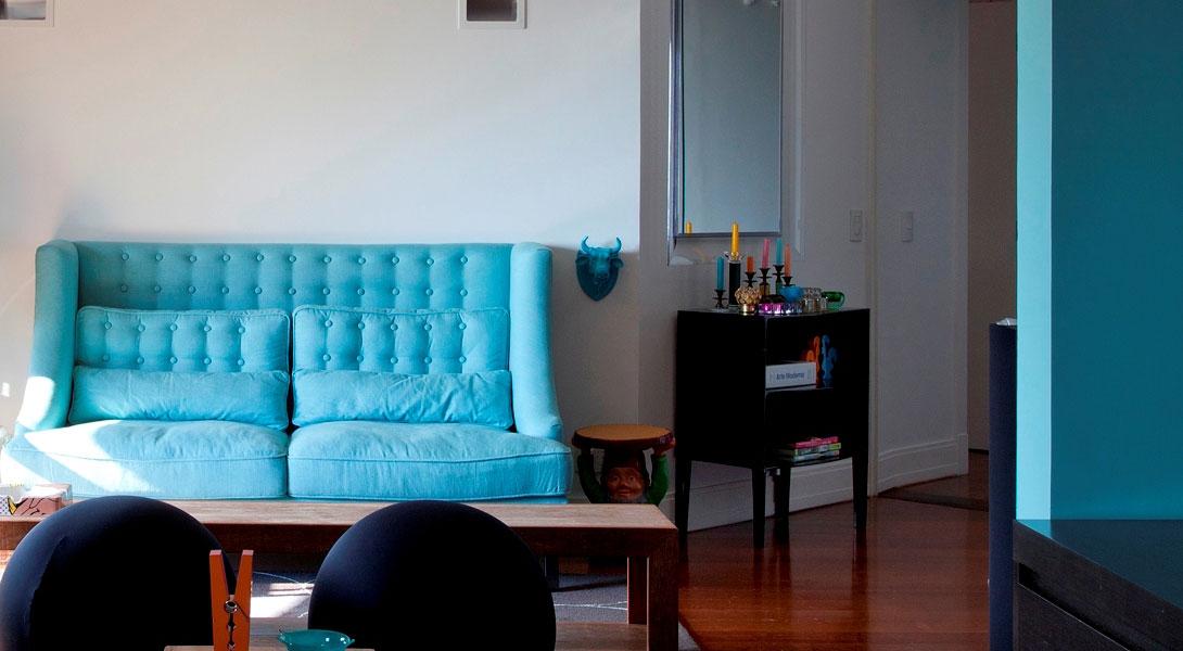 Apostamos em uma paleta ousada que mistura diversos tons de roxo, azul, amarelo e vermelho. O azul do sofá exalta a estética retrô da decoração, combinando com a parede da sala de jantar e os objetos espalhados pelo living. A mesa de centro em madeira de demolição, na verdade é um banco.