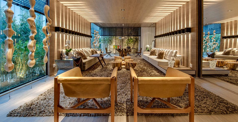 O living da imprensa decorado pela arquiteta e urbanista Carla Felippi tem estilo contemporâneo e intimista. No ambiente, os tons amadeirados e a integração com o jardim externo dão um clima aconchegante no local.