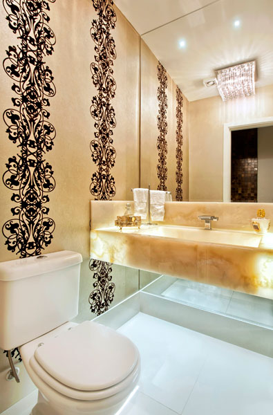 O banheiro desenvolvido pelas arquitetas Cristiane Maciel e Sony Luczysyn, da Arqtríade tem estilo clássico aliado à praticidade, elegância e conforto. Para dar um toque de sofisticação no ambiente, as arquitetas utilizaram  papel de parede estampado e instalaram uma cuba de mármore ônix com iluminação sob o tampo.