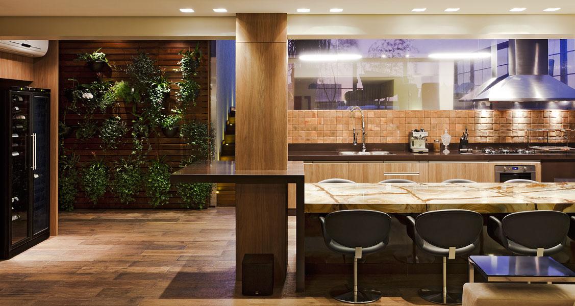 No espaço gourmet, as paredes foram demolidas para integrar completamente os ambientes. O piso é porcelanato que imita madeira e faz a setorização de ambientes. Desta forma, o revestimento confere aconchego e ao mesmo tempo, praticidade na manutenção. Projetado pela Borges Godoy Arquitetura e Interiores.