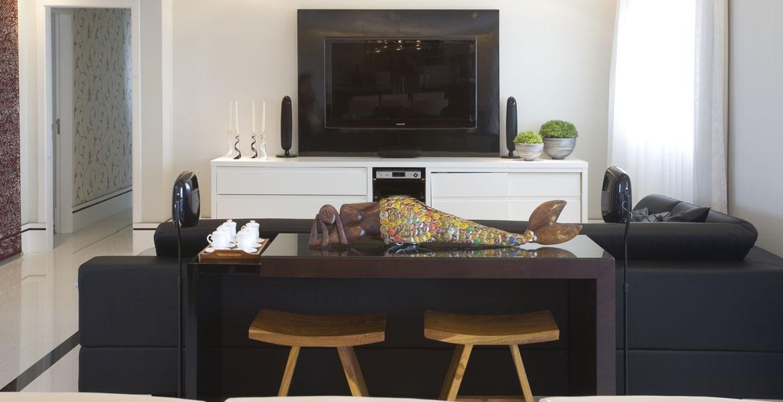 Para o living, Adriana Scartaris aplicou a técnica para ativar as áreas de trabalho, amigos e criatividade. Sobre o aparador, uma escultura reciclada em madeira e tampinhas de garrafa ativa, através de sua temática e elemento metal aplicado, as áreas da criatividade e dos amigos.