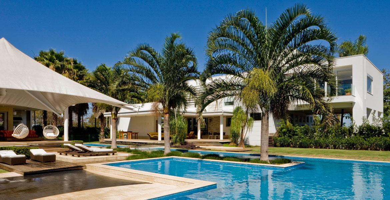Neste projeto da arquiteta Consuelo Jorge a piscina é abraçada pela casa e área de lazer criando uma integração e harmonia perfeita entre a arquitetura e a vegetação do local.
