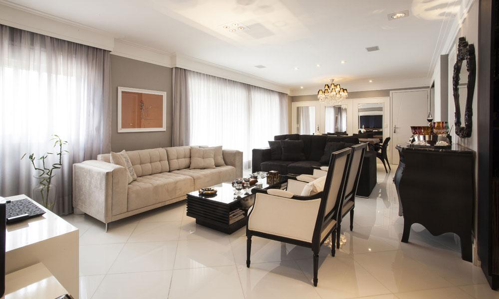 A ampla sala integrada aos ambientes sociais é composta com móveis clássicos em tons de creme e preto