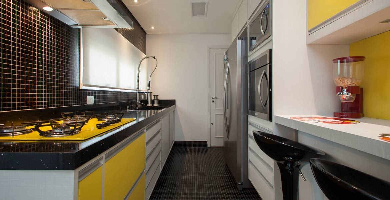 Nesta cozinha, a arquiteta Patrícia Duarte apostou nas tendências do mercado, utilizando o jogo monocromático do amarelo com o preto. O piso e a parede da pia foram revestidos por pastilhas pretas.