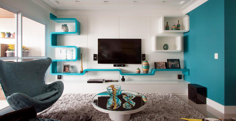 Com design sinuoso, estante em laca azul-turquesa e nichos em laca branca compõem o décor da sala de TV.