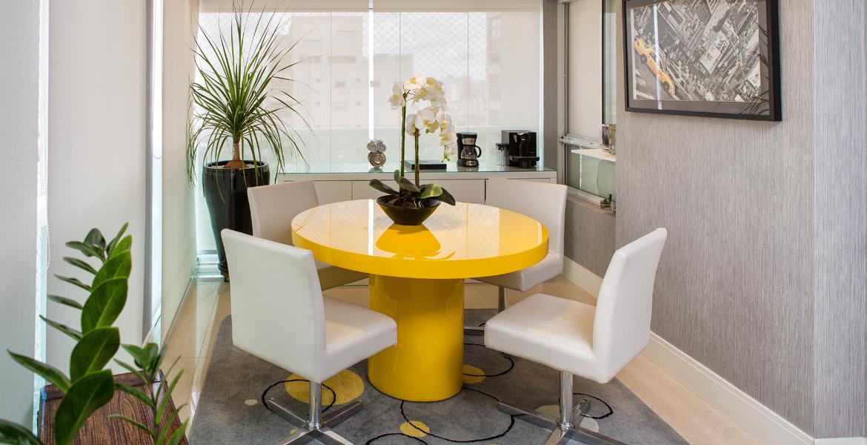 Nesta sala de almoço, a mesa redonda amarela é o grande destaque. A cor deixa o ambiente alegre, ideal para as refeições. O clima fresco fica por conta das plantas distribuídas harmoniosamente. Projeto da designer de interiores Dinna Albuquerque.