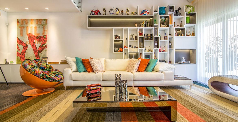 Na sala de estar, os móveis são mais lineares a fim de aproveitar o ambiente. Para valer-se da iluminação natural da área externa, duas portas balcão foram colocadas no lugar de duas janelas.