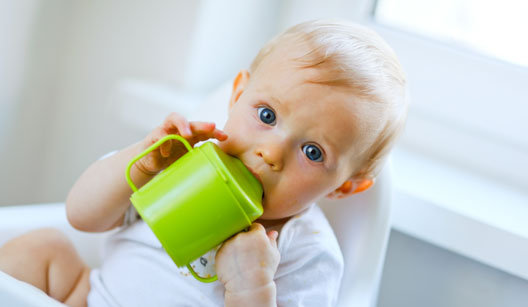 Bebê na cadeirinha bebendo em copinho