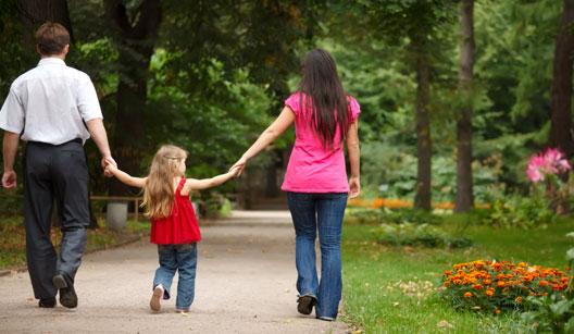 Pais andando com criança no parque