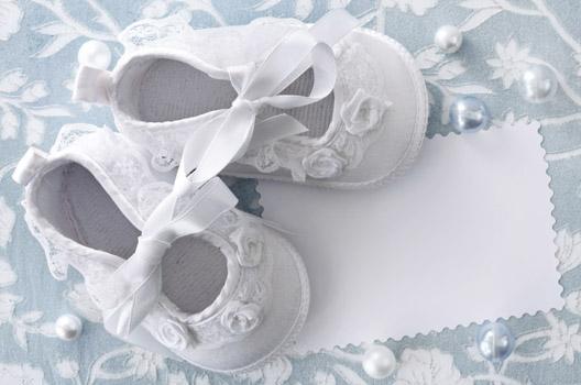 sapatos brancos de bebê em fundo de renda
