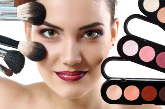 Mulher maquiada segurando pincéis e sombras