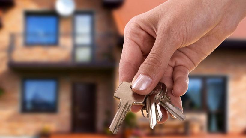 mão segurando chaves com imóvel ao fundo