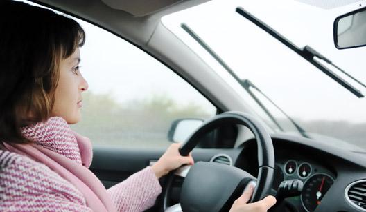 Mulher dirigindo na chuva