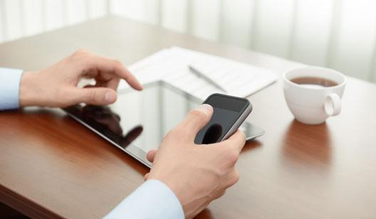 Homem usando tablet e smartphone