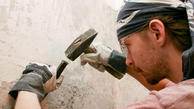homem removendo acabamento da parede