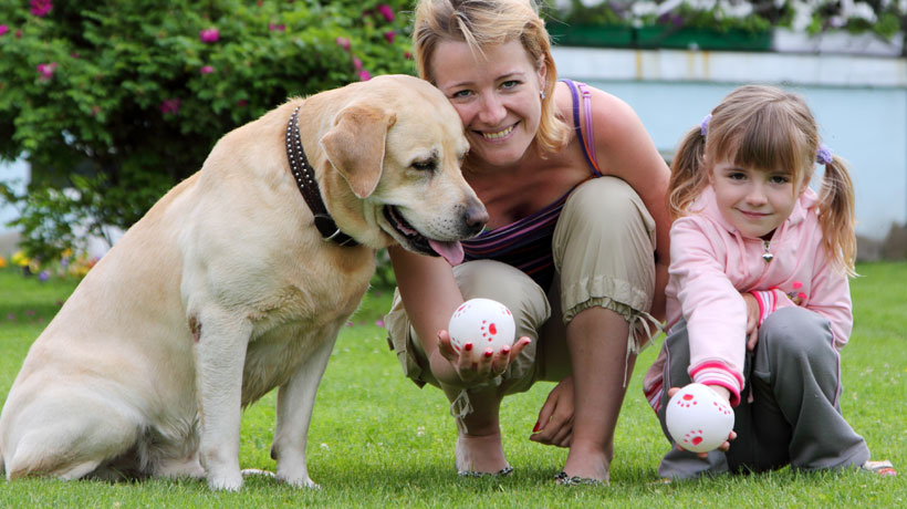 Mãe e filha brincando com cachorro