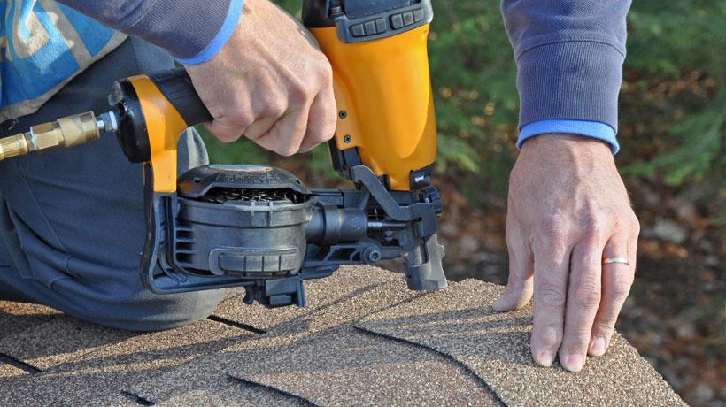 homem instalando telhas asfálticas