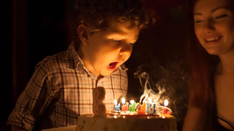 Criança apagando as velas do bolo de aniversário