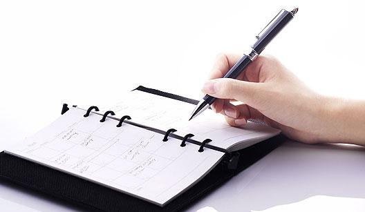 Mulher escrevendo na agenda