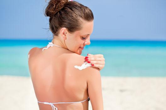Mulher na praia passando protetor solar