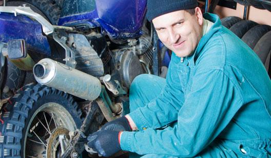 homem trabalhando em motocicleta na oficina