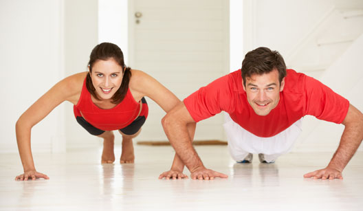 Homem e mulher fazendo flexão