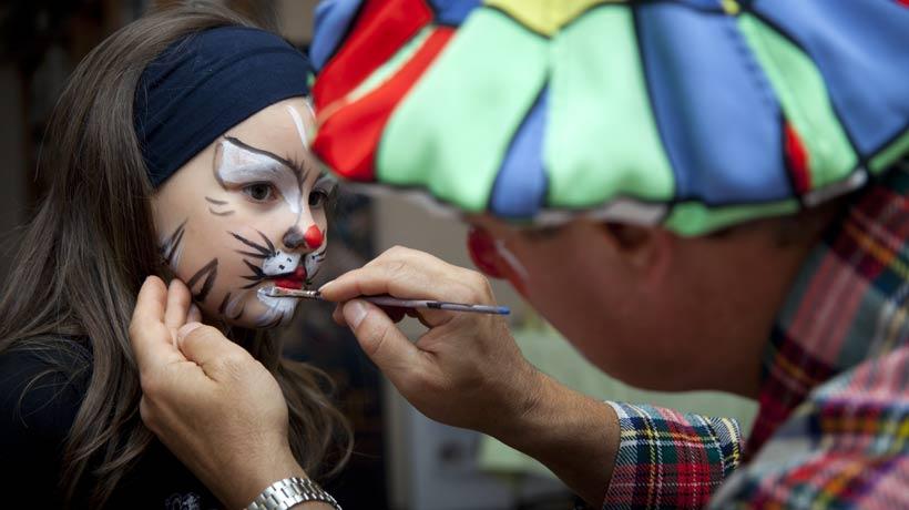 criança sendo pintada por palhaço