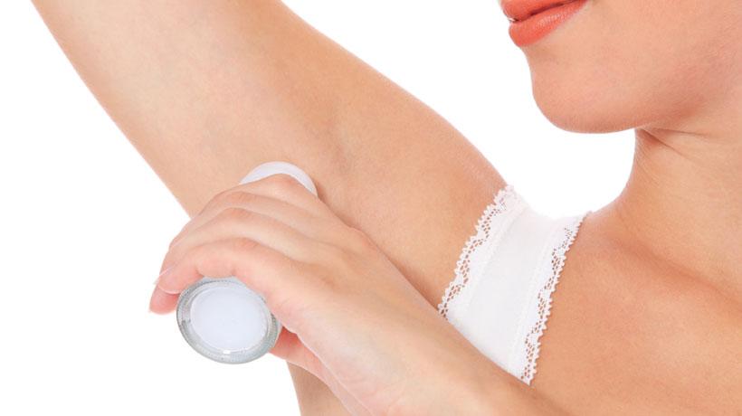 Mulher passando antitranspirante roll-on