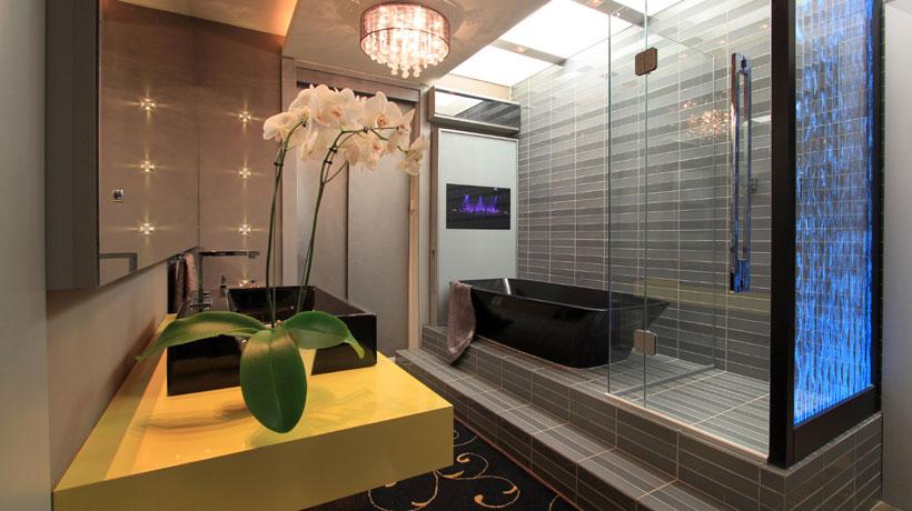 Banheiro com banheira preta e bancada amarela
