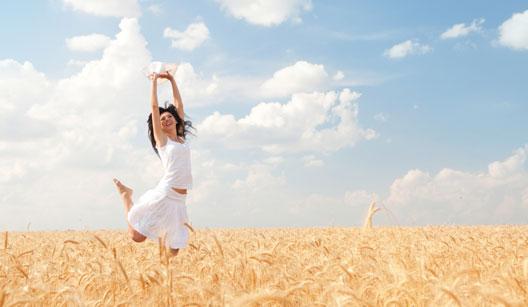 Mulher pulando numa plantação de trigo