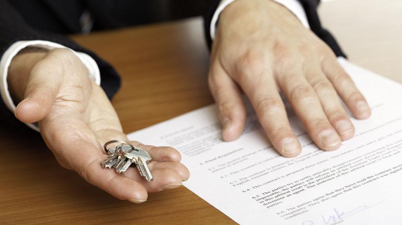 pessoa com contrato e segurando chaves