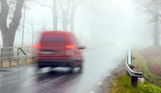 Carro dirigindo em estrada com neblina