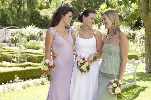 Noiva com duas amigas em um jardim