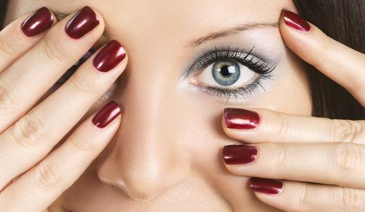 mulher maquiada com unhas vermelhas