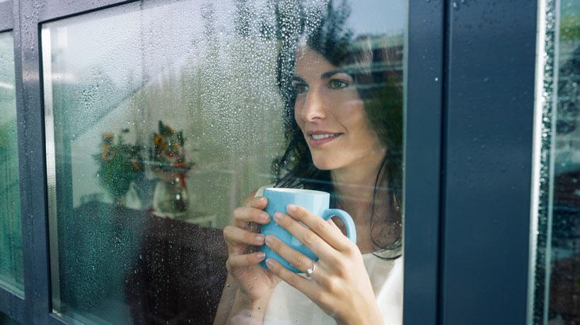 Mulher olhando pela janela com vidro respingado