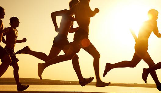 Grupo de pessoas correndo na praia