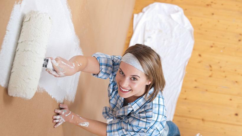 mulher pintando a parede