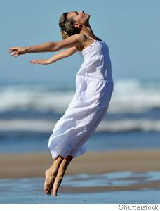 Mulher pulando na praia