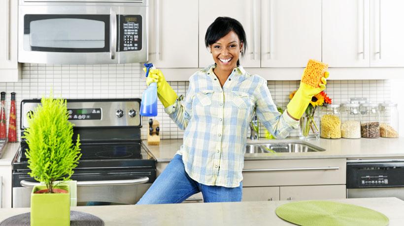 Mulher sorrindo com produtos de limpeza nas mãos