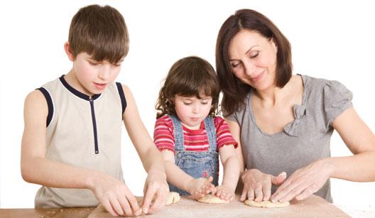 mãe fazendo biscoitos com filhos