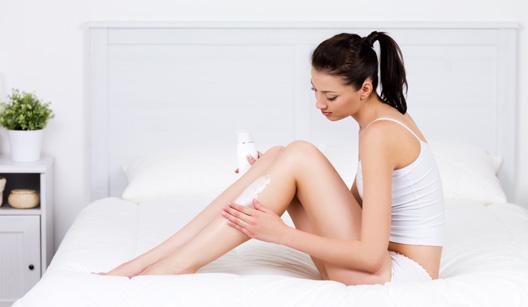 Mulher passando creme na perna