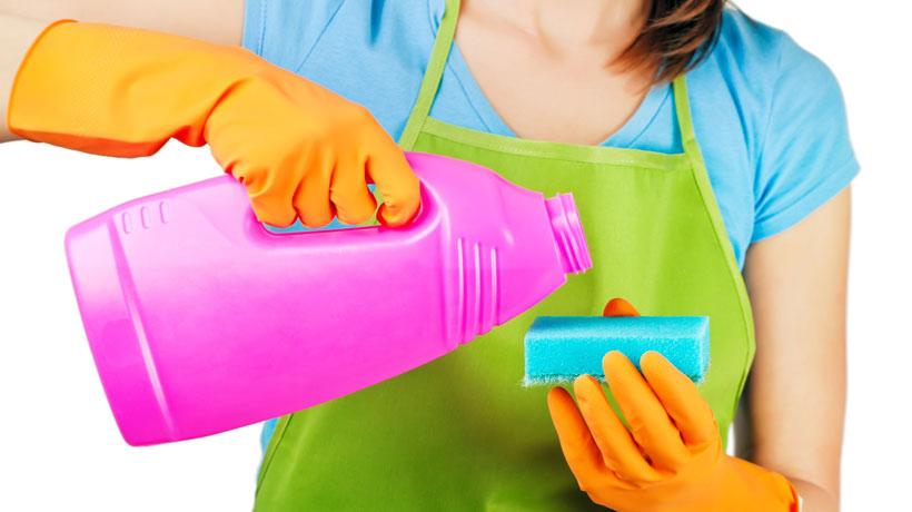mulher colocando produto de limpeza em esponja