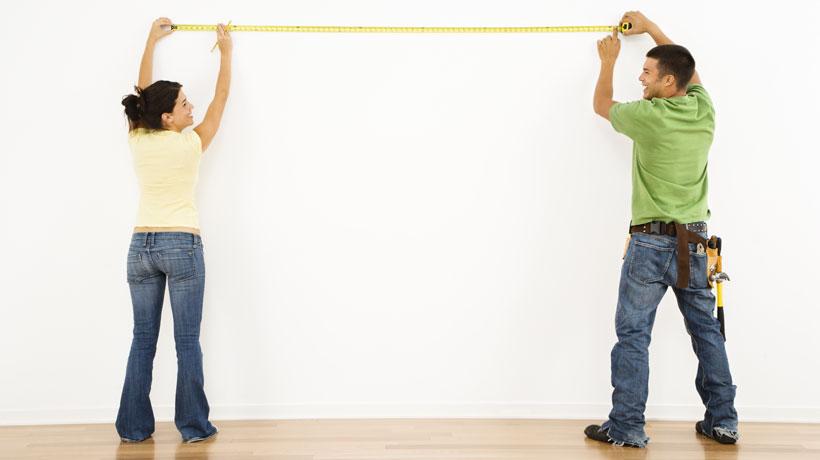 Casal medindo a parede interna da casa