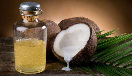 Metade do coco com um vidro de óleo