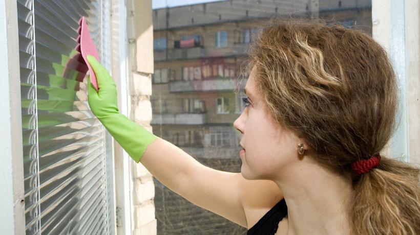 Mulher limpando persiana