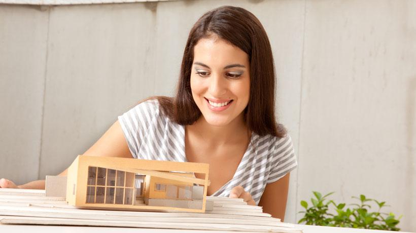 Mulher olhando maquete de casa