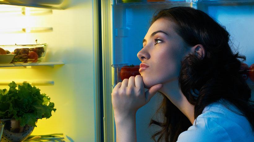 mulher em dúvida com a geladeira aberta