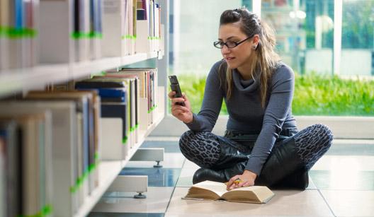Mulher usando celular na biblioteca
